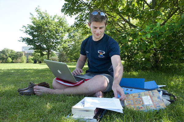 A male student sat on grass with a laptop, with books and notes beside him