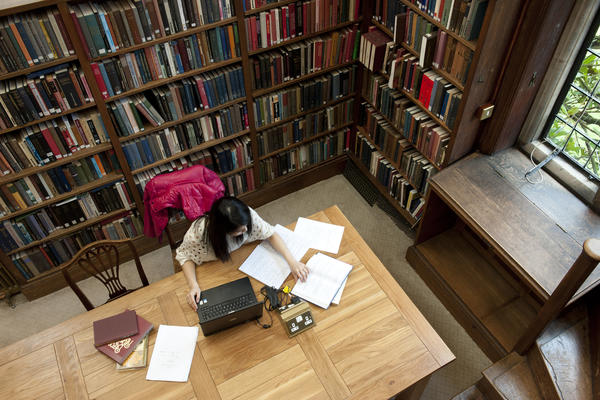 A female student working in the library at Somerville College