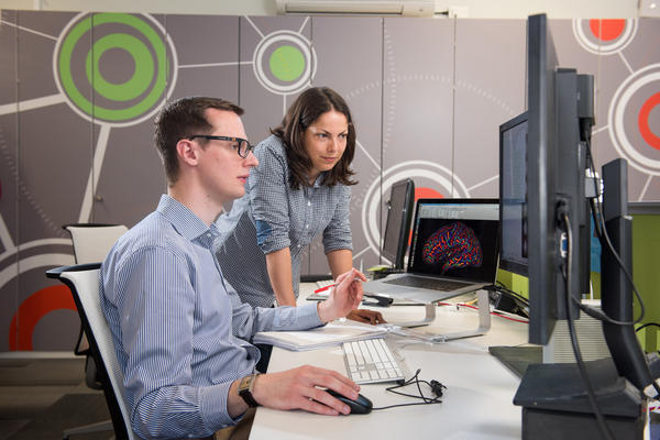 A student and supervisor looking at computer screens, discussing brain imaging data