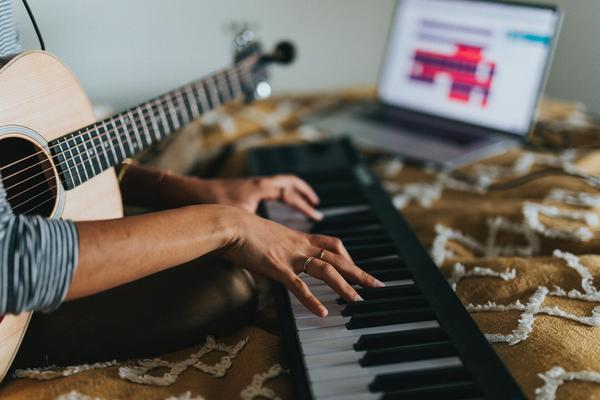 hand playing electronic keyboard with guitar in hand