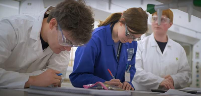 A woman and two men in a chemistry lab making notes